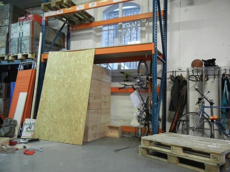 L'étagère avec les vélos stockés en vertical en bas, la porte à gauche et le rangement à l'intérieur